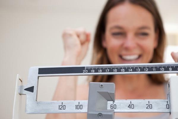 mulher feliz sorridente em frente a uma balança de peso