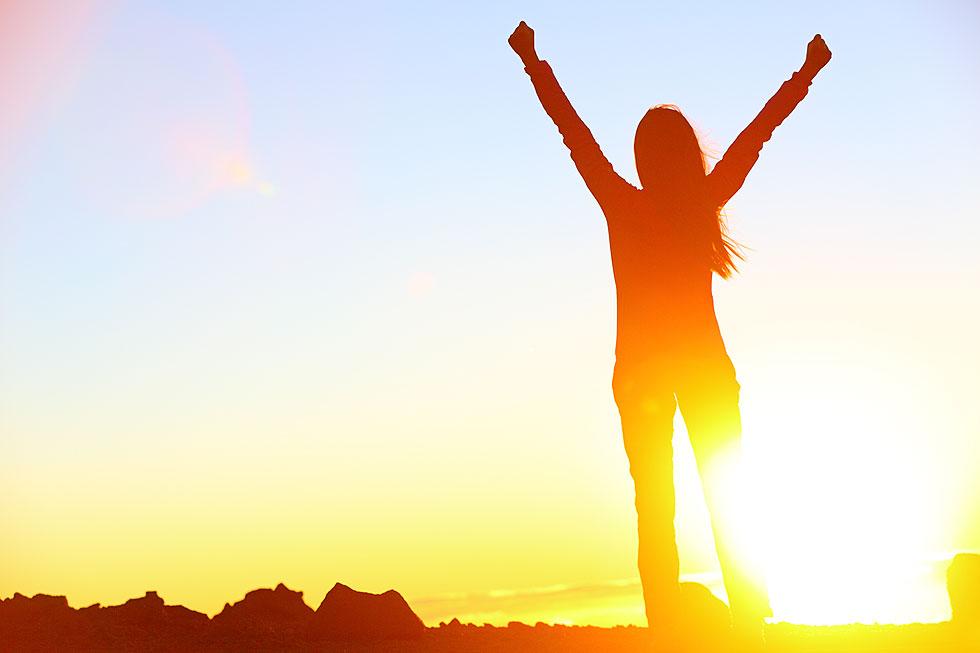 mulher feliz com os braços levantados