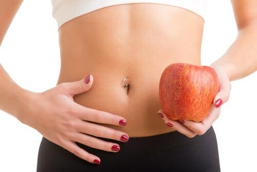 mulher em forma segurando uma maçã