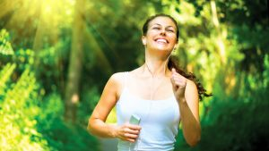 imagem de uma mulher fazendo umam caminhada sorrindo
